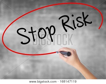 Woman Hand Writing Stop Risk With Black Marker Over Transparent Board