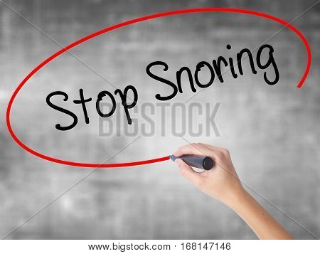 Woman Hand Writing Stop Snoring With Black Marker Over Transparent Board