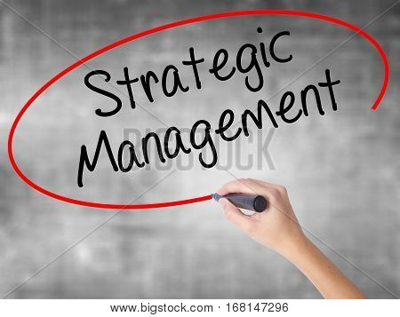 Woman Hand Writing Strategic Management With Black Marker Over Transparent Board.