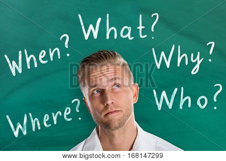 Young Man Thinking About Five Ws Questions Against Chalkboard