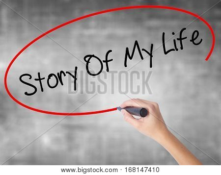 Woman Hand Writing Story Of My Life With Black Marker Over Transparent Board