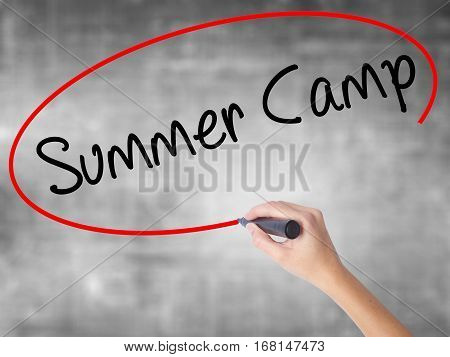 Woman Hand Writing Summer Camp With Black Marker Over Transparent Board