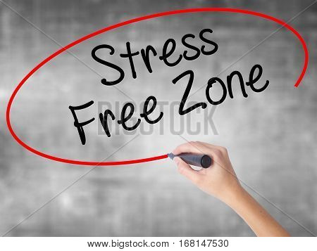 Woman Hand Writing Stress Free Zone With Black Marker Over Transparent Board