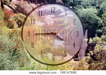 Time change concept. Double exposure of female hands holding clock and landscape background