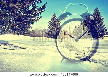 Time change concept. Double exposure of alarm clock and winter landscape background