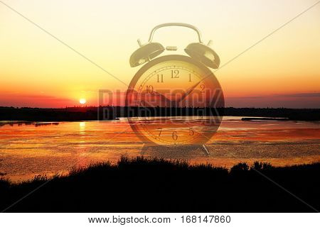 Time change concept. Double exposure of alarm clock and landscape background
