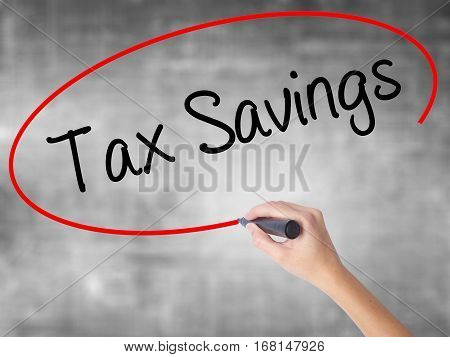 Woman Hand Writing Tax Savings With Black Marker Over Transparent Board