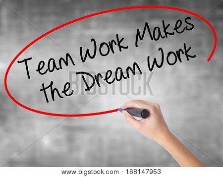 Woman Hand Writing Team Work Makes The Dream Work With Black Marker Over Transparent Board