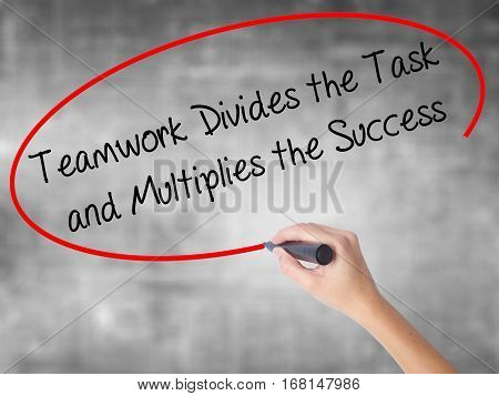 Woman Hand Writing Teamwork Divides The Task And Multiplies The Success With Black Marker Over Trans