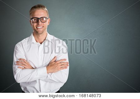 Portrait Of A Young Smiling Businessman Against Grey Background