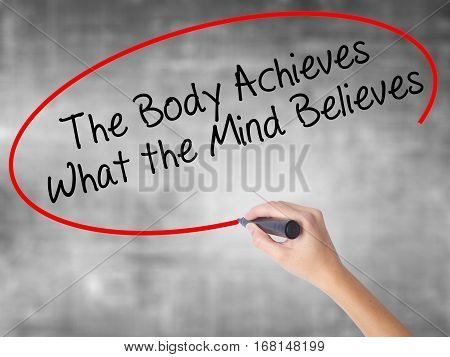 Woman Hand Writing The Body Achieves What The Mind Believes With Black Marker Over Transparent Board