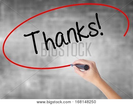 Woman Hand Writing Thanks! With Black Marker Over Transparent Board