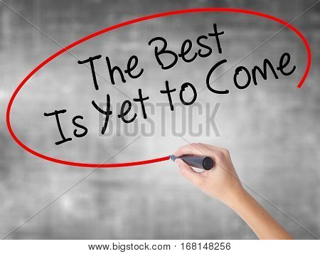 Woman Hand Writing The Best Is Yet To Come With Black Marker Over Transparent Board