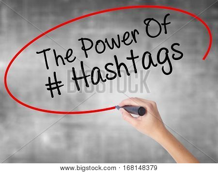Woman Hand Writing The Power Of Hashtags With Black Marker Over Transparent Board