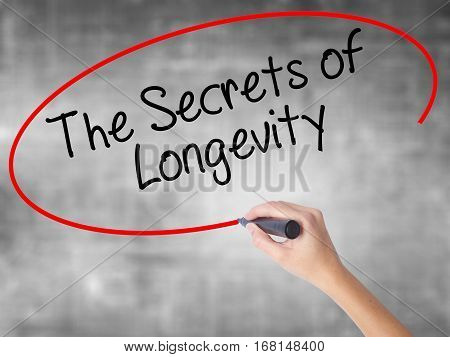 Woman Hand Writing The Secrets Of Longevity With Black Marker Over Transparent Board