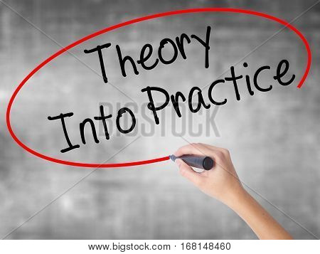 Woman Hand Writing Theory Into Practice With Black Marker Over Transparent Board