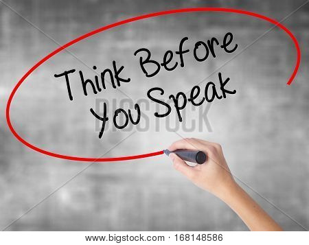Woman Hand Writing Think Before You Speak With Black Marker Over Transparent Board