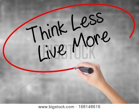 Woman Hand Writing Think Less Live More With Black Marker Over Transparent Board