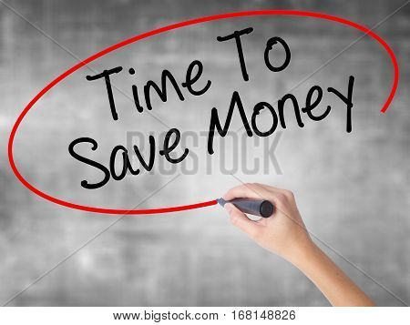 Woman Hand Writing Time To Save Money  With Black Marker Over Transparent Board.
