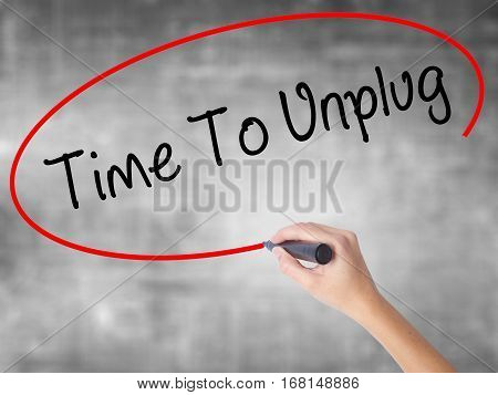 Woman Hand Writing Time To Unplug With Black Marker Over Transparent Board