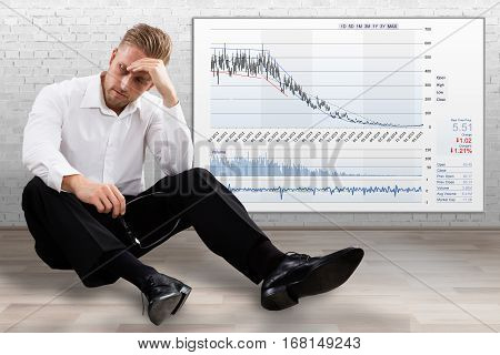 Young Upset Stock Broker Sitting Near The Deflation Graph On Wall