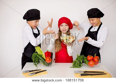 three young chefs near the white table evaluate a salad isolated. disgusting