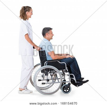 A Female Caretaker Pushing Disabled Male Patient On Wheelchair Against White Background