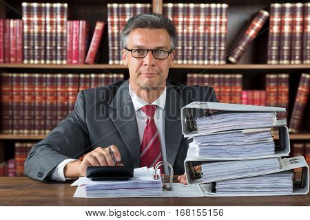 Portrait Of A Male Accountant Working With Stacked Folders On Wooden Desk In Courtroom