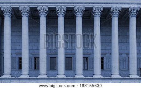 A building facade with corinthian columns in a row (colonnade). The neoclassical building style resembles a law court / courthouse, university, library or public administration building. Blue color tone.
