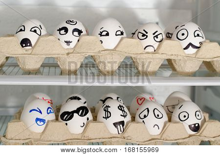 Two trays with painted smiles on the eggs on the refrigerator shelves close up