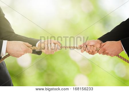 Close-up Of A Two Businessman Pulling Rope In Opposite Direction
