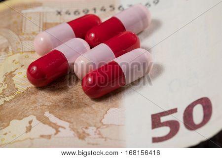 Red and pink antibiotics capsule and money