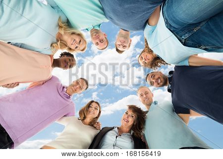 Portrait Of A Happy Multiethnic Friends Forming Huddle Against Sky
