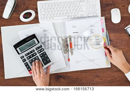 High Angle View Of A Auditor Analyzing Bills Using Magnifying Glass At Office Desk