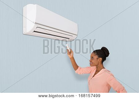 A Smiling African Woman Operating Air Conditioner With Remote At Home