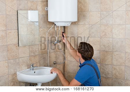 Technician Repairing Broken Electric Boiler At Home