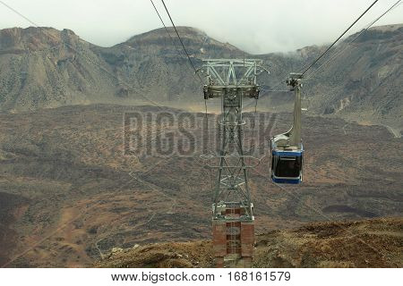 Blue ropeway cable car over crater of eruption desert lava valley with grey and brown volcanic slopes surface on mountain scene on cloudy sky background