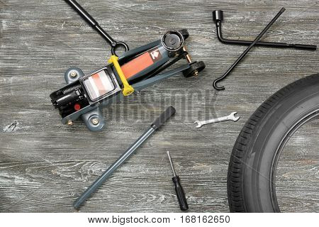 Car jack with tools and tire on wooden background
