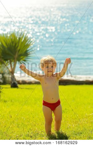 Cute Cheerful Baby Boy In Red Trunks Raises Hands