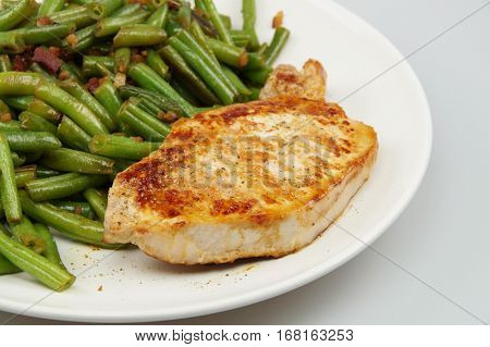 pork chop steak with green beans served on white plate