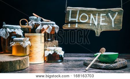 Honey jars assortment. Bowl of honey and dipper for tasting. Wood sign above the counter