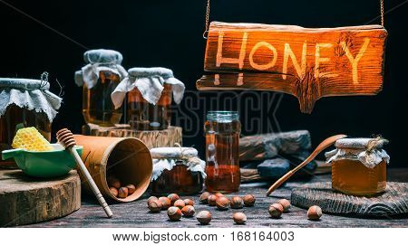 Hanging wooden sign of traditional honey shop. Honey jars and nuts in amber lighting