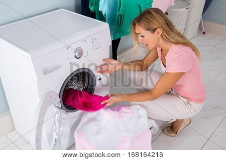 Shocked upset Young Woman Looking At Stained Bleached Cloth In Washing Machine At Laundry Room