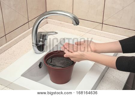 Water shortage concept. Woman holding hands under tap