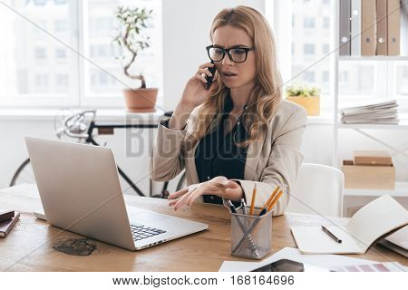 Talking about details. Gorgeous businesswoman in smart casual wear talking on the mobile phone and gesturing while sitting at her working place in creative office