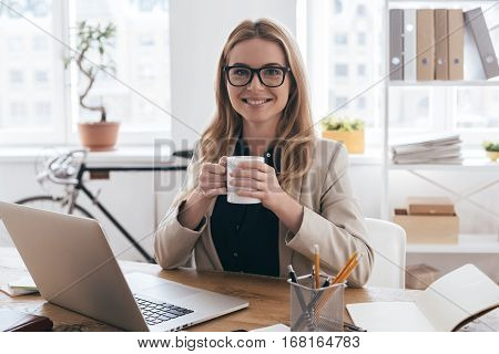 Time for coffee break. Young woman in smart casual wear holding a cup of coffee and looking at camera while sitting at her working place in creative office