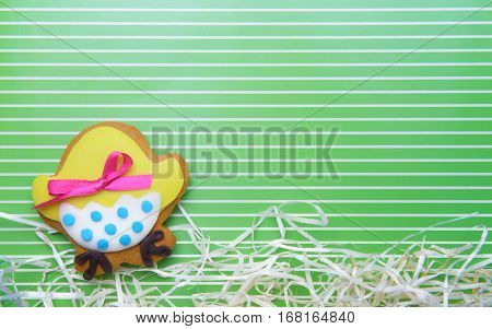 Decorative gingerbread Easter cookie with paper streamers on green striped background