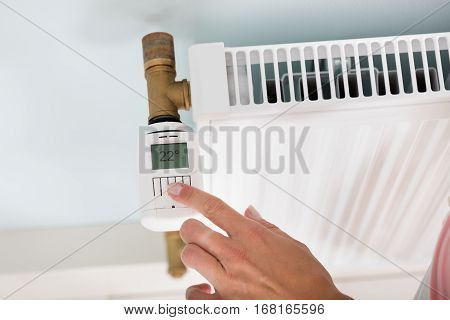 Close-up Of A Person's Hand Adjusting Temperature To Reduce Heat On Digital Thermostat