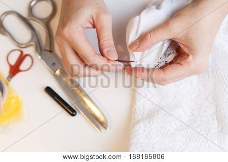 Woman unpick fabric on table
