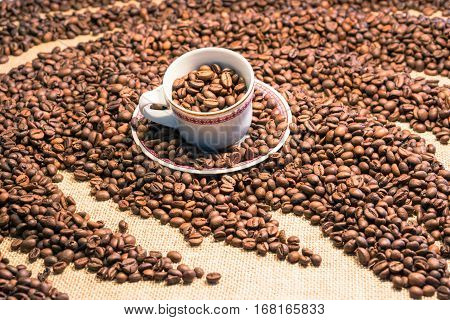 Coffee cup full of beans emerging from wavy grain heap close up image with blurred background - Concept of product freshness with warm tones focus inside small mug